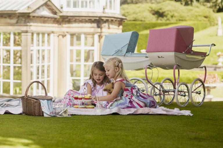 two girls having a picnic next to silver cross dolls' prams